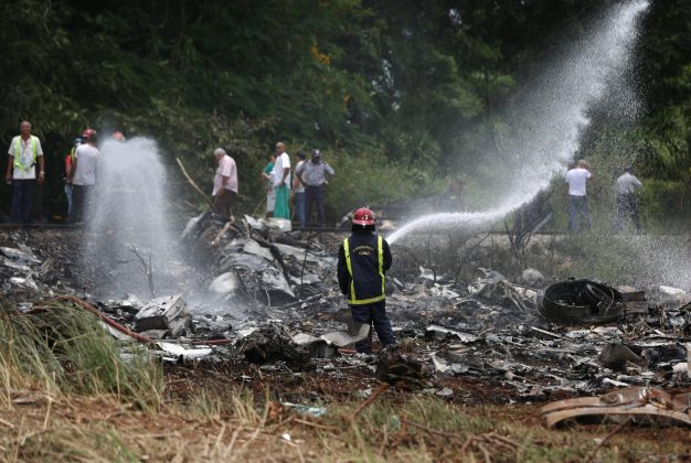 Firefighters work in the wreckage of a Boeing 737 plane that crashed in the agricultural area of Boyeros, around 20 km (12 miles) south of Havana, shortly after taking off from Havana's main airport in Cuba, May 18, 2018. REUTERS/Alexandre Meneghini