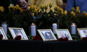 Candles are lit behind images of the victims killed in a shooting at Santa Fe High School during a vigil in League City, Texas, U.S., May 20, 2018. REUTERS/Jonathan Bachman NO RESALES. NO ARCHIVES.