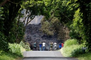 Journalists and Hawaii National Guard soldiers document a lava flow on Highway 137 southeast of Pahoa during ongoing eruptions of the Kilauea Volcano in Hawaii, U.S., May 20, 2018. REUTERS/Terray Sylvester