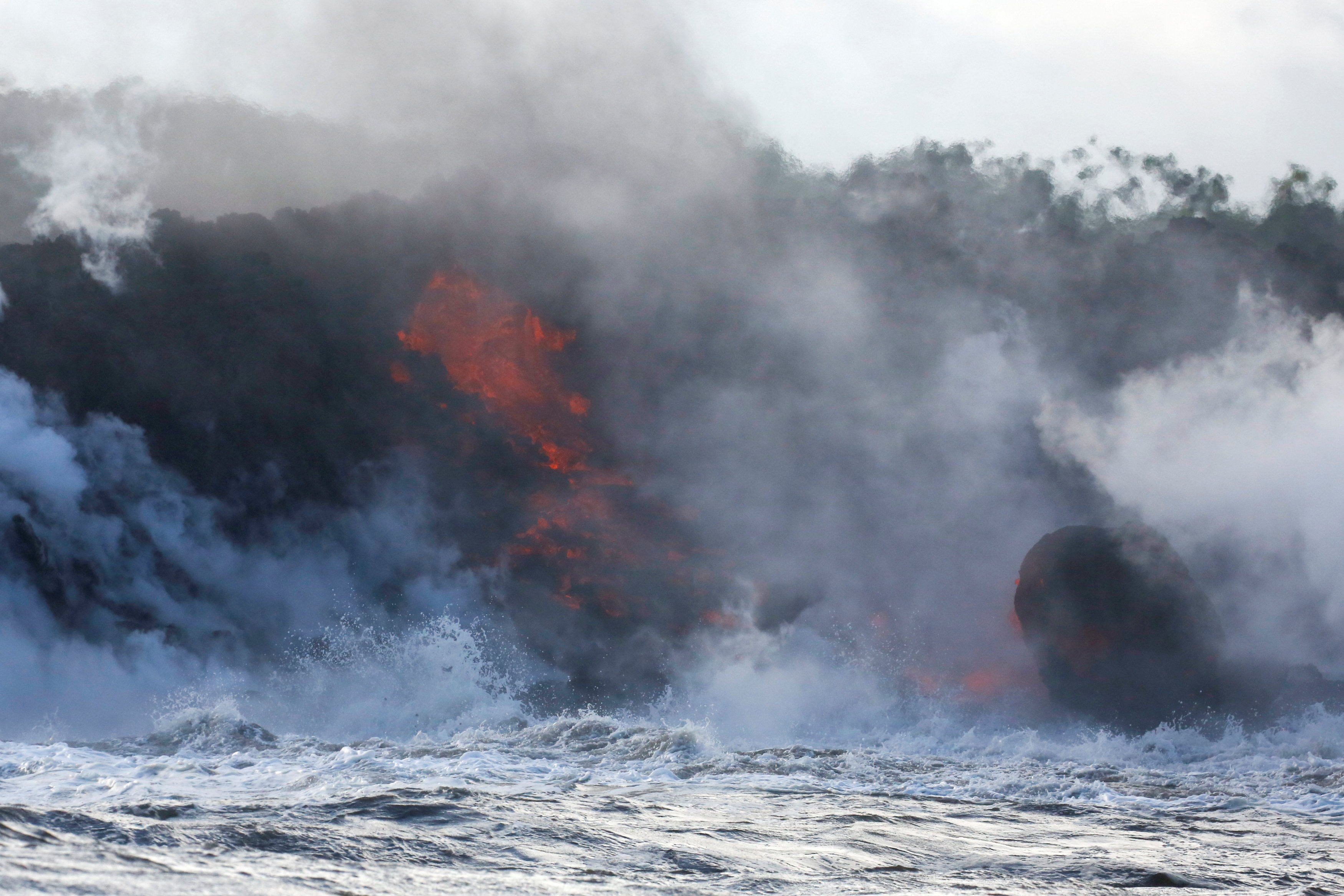 Lava flows into the Pacific Ocean southeast of Pahoa during ongoing eruptions of the Kilauea Volcano in Hawaii, U.S., May 20, 2018. REUTERS/Terray Sylvester