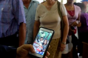 An evangelical pastor shows a picture of Ronni Pupo and Yurisel Miranda, victims of the Boeing 737 plane crash, during a religious ceremony in a church in Havana, Cuba, May 20, 2018. REUTERS/Alexandre Meneghini