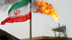 FILE PHOTO: A gas flare on an oil production platform in the Soroush oil fields is seen alongside an Iranian flag in the Persian Gulf, Iran, July 25, 2005. REUTERS/Raheb Homavandi//File Pho