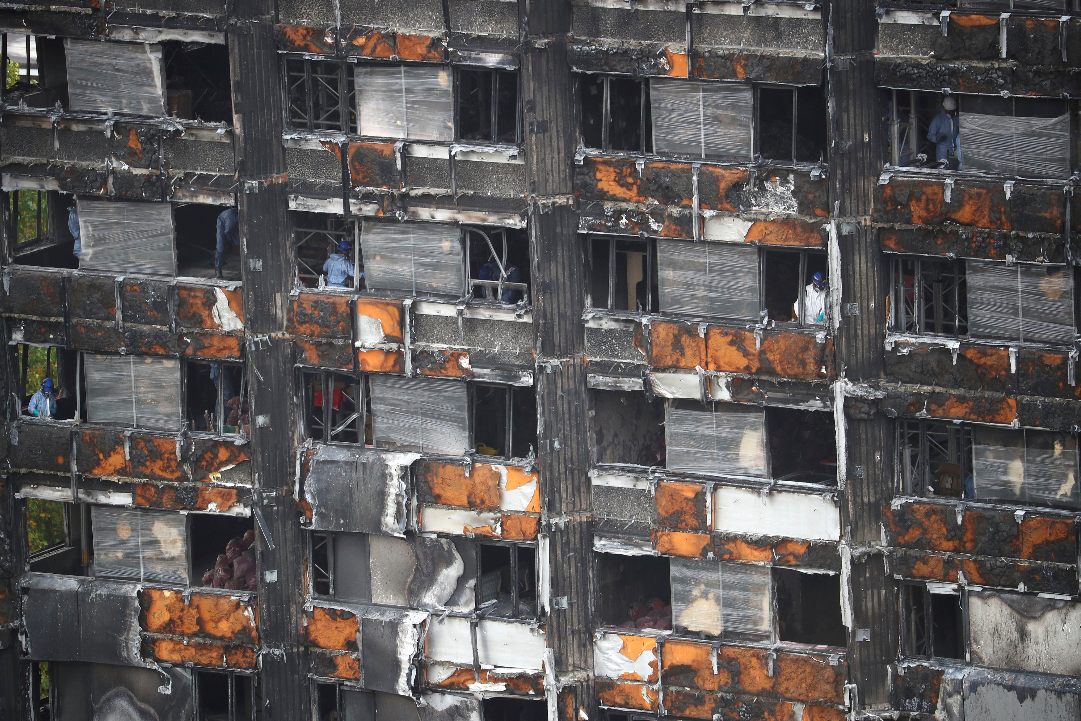 FILE PHOTO: Workers stand inside the burnt out remains of the Grenfell tower in London, Britain, October 16, 2017. REUTERS/Hannah Mckay/File Photo