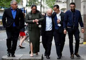 Marcio and Andreia Gomes, parents of Logan Gomes, are comforted as they arrive for a commemoration hearing at the opening of the inquiry into the Grenfell Tower disaster, in London, Britain May 21, 2018. REUTERS/Henry Nicholls