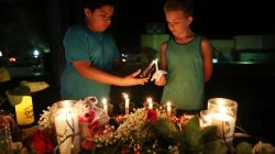 Christian Cardenas 10, helps Jaydon Johnson 8, light a candle during a vigil for the victims of a shooting at Santa Fe High School that left several dead and injured in Santa Fe, Texas, U.S., May 18, 2018. REUTERS/Pu Ying Huang