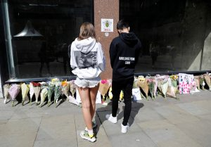 People wearing Ariana Grande sweatshirts look at tributes left in St Anne's Square on the first anniversary of the Manchester Arena bombing, in Manchester, Britain, May 22, 2017. REUTERS/Darren Staples