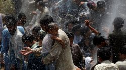 Men and children cool off from the heatwave, as they are sprayed with water jetting out from a leaking water pipeline in Karachi, Pakistan May 22, 2018. REUTERS/Akhtar Soomro