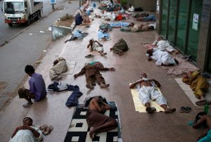 Residents sleep on a building pavement, to escape heat and frequent power outage in their residence area Karachi, Pakistan. REUTERS/Akhtar Soomro