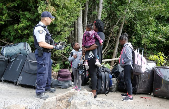 FILE PHOTO: A family who identified themselves as being from Hait, are confronted by a Royal Canadian Mounted Police (RCMP) officer as they try to enter into Canada from Roxham Road in Champlain, New York, U.S., August 7, 2017. REUTERS/Christinne Muschi/File Phot