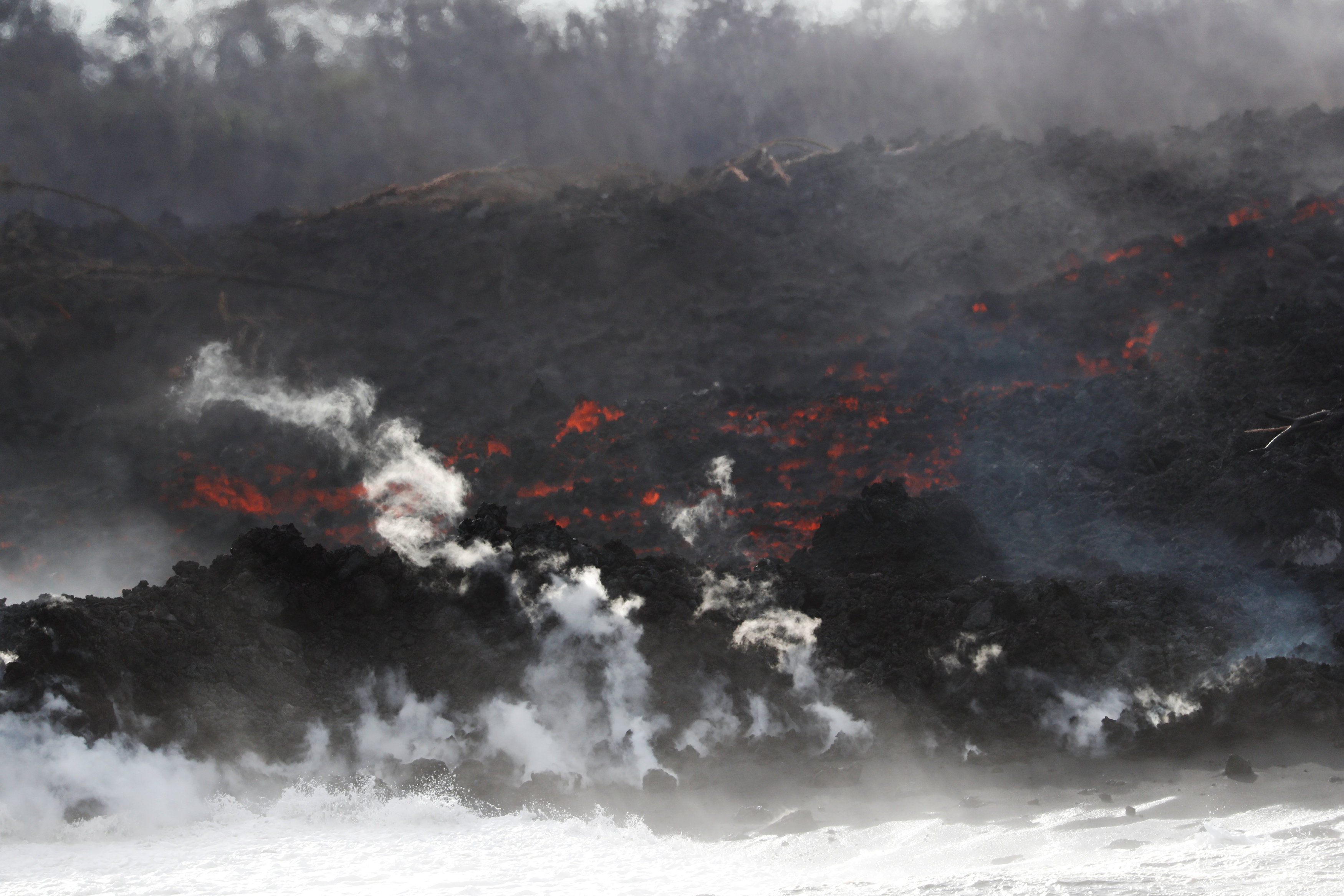 After crossing Highway 137, lava pours into the ocean during the eruption of the Kilauea Volcano near Pahoa, Hawaii, U.S., May 24, 2018. REUTERS/Marco Garcia