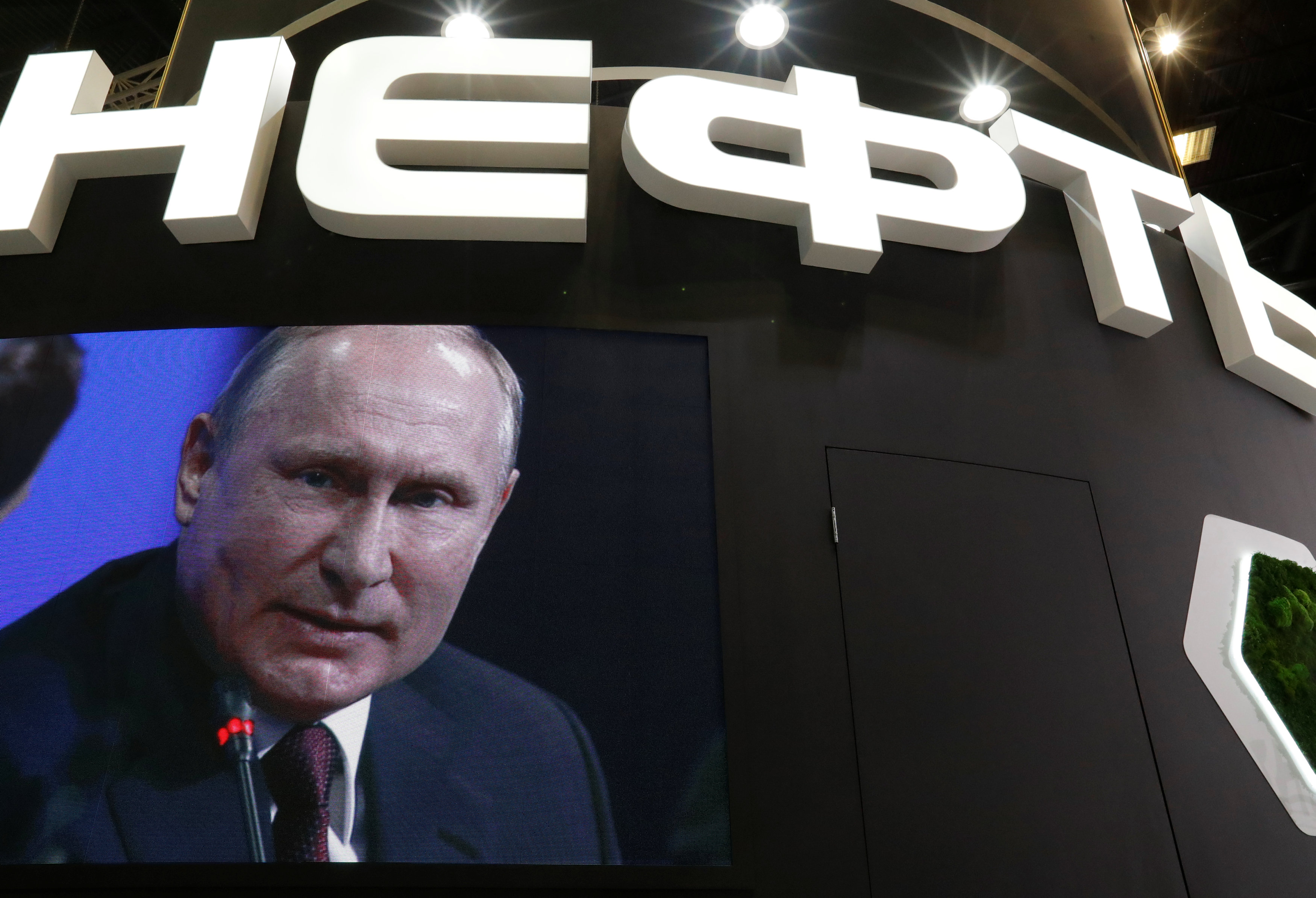 Russian President Vladimir Putin is seen on a screen at the stand of Russian state oil major Rosneft during the St. Petersburg International Economic Forum (SPIEF), Russia May 25, 2018. REUTERS/Sergei Karpukhin