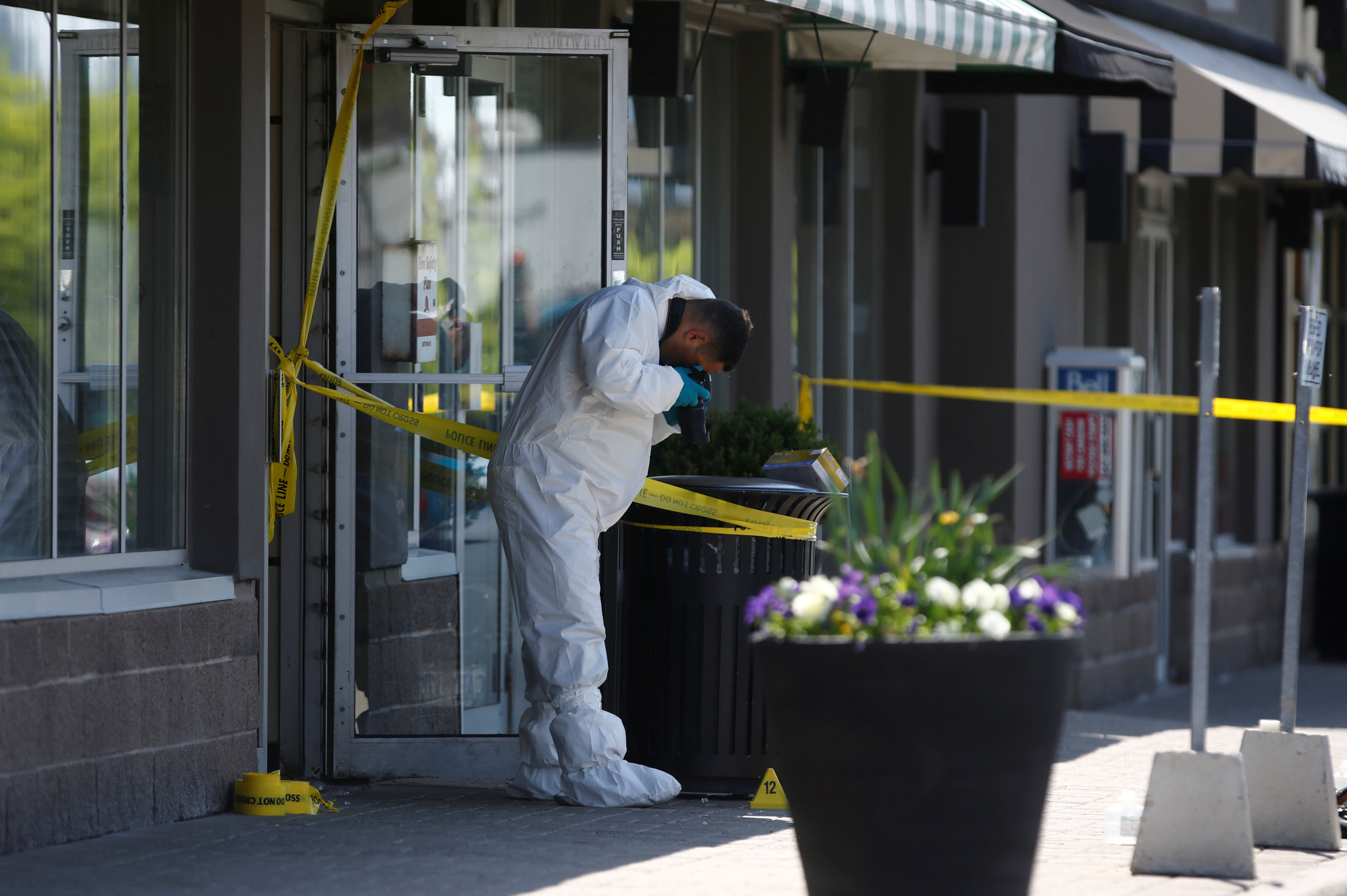 A police forensic investigator photographs evidence at Bombay Bhel restaurant, where two unidentified men set off a bomb late Thursday night, wounding fifteen people, in Mississauga, Ontario, Canada May 25, 2018. REUTERS/Mark Blinch