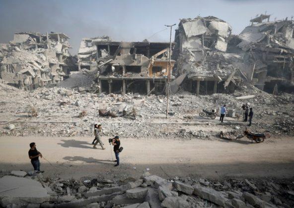 A Syrian army soldier walks past the rubble of damaged buildings in al-Hajar al-Aswad, Syria May 21, 2018. REUTERS/Omar Sanadiki