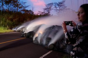 A news reporter takes pictures of the Kilauea lava flow that crossed Pohoiki Road near Highway 132, near Pahoa, Hawaii, U.S., May 28, 2018. REUTERS/Marco Garcia