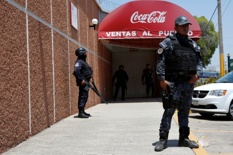 FILE PHOTO: Police officers guard the entrance of the Coca-Cola FEMSA distribution plant after it closes down due to the issues of security and violence during the campaign rally of Independent presidential candidate Margarita Zavala (unseen) in Ciudad Altamirano, Guerrero state, Mexico April 3, 2018. REUTERS/Ginnette Riquelme/File Photo