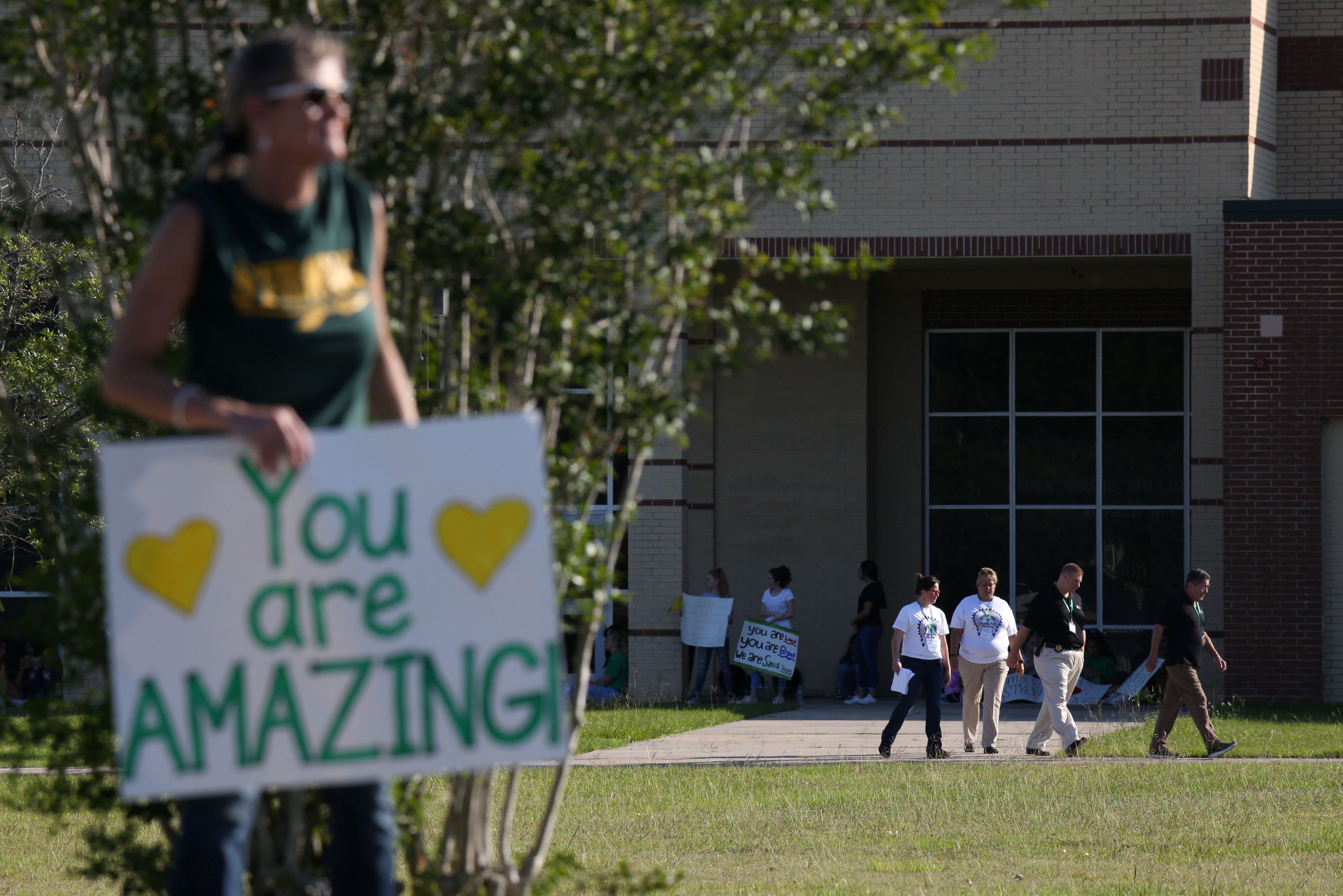 Community members stood in support as students and administrators returned for the first day of class since a deadly mass shooting in Santa Fe, Texas, U.S., May 29, 2018. REUTERS/Pu Ying Huang