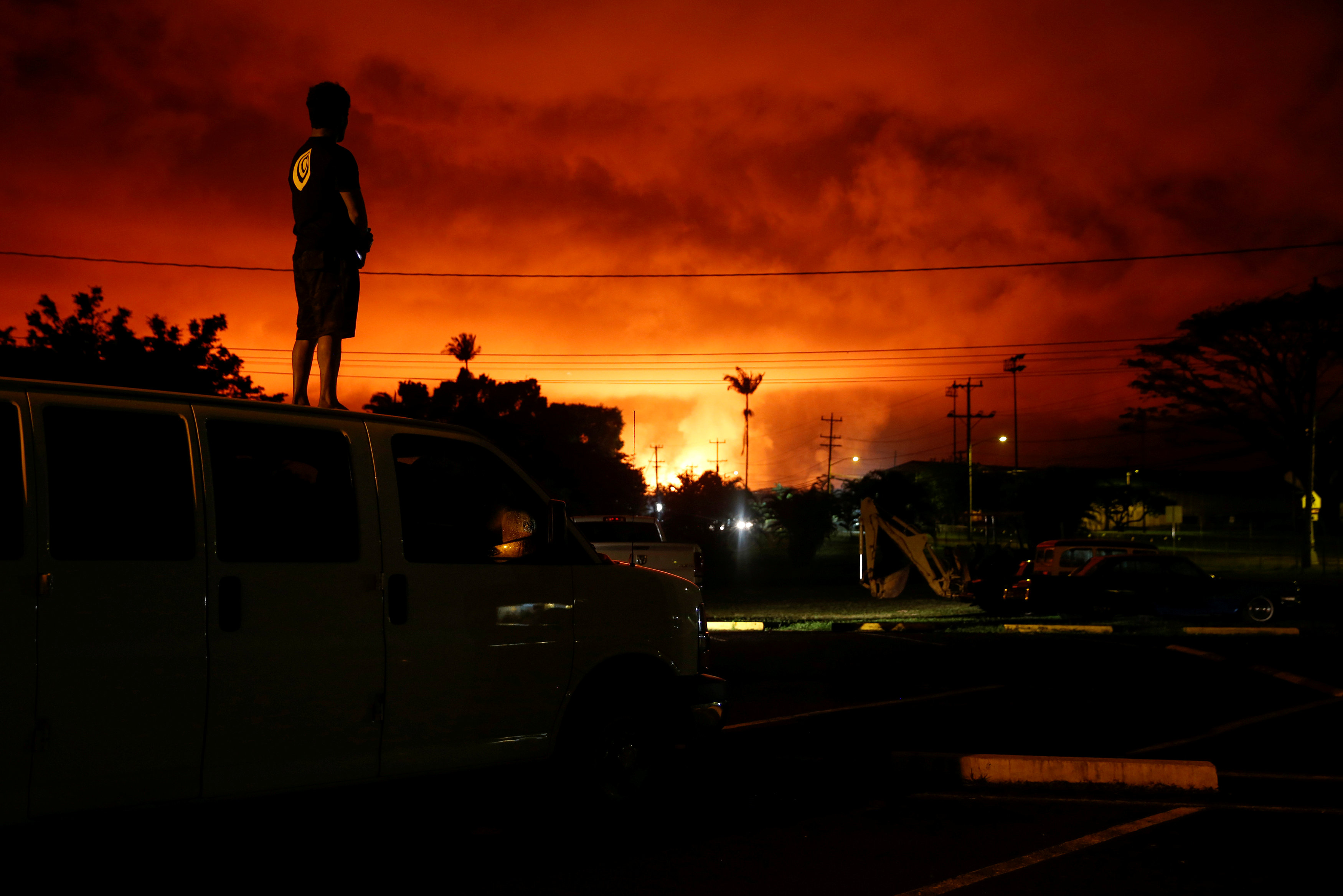 Darryl Sumiki, 52, of Hilo, watches as lava lights up the sky above Pahoa during ongoing eruptions of the Kilauea Volcano in Hawaii, U.S., June 2, 2018. REUTERS/Terray Sylvester