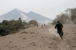 A police officer runs away from a new pyroclastic flow spewed by the Fuego volcano in the community of San Miguel Los Lotes in Escuintla, Guatemala, June 4, 2018. REUTERS/Luis Echeverria
