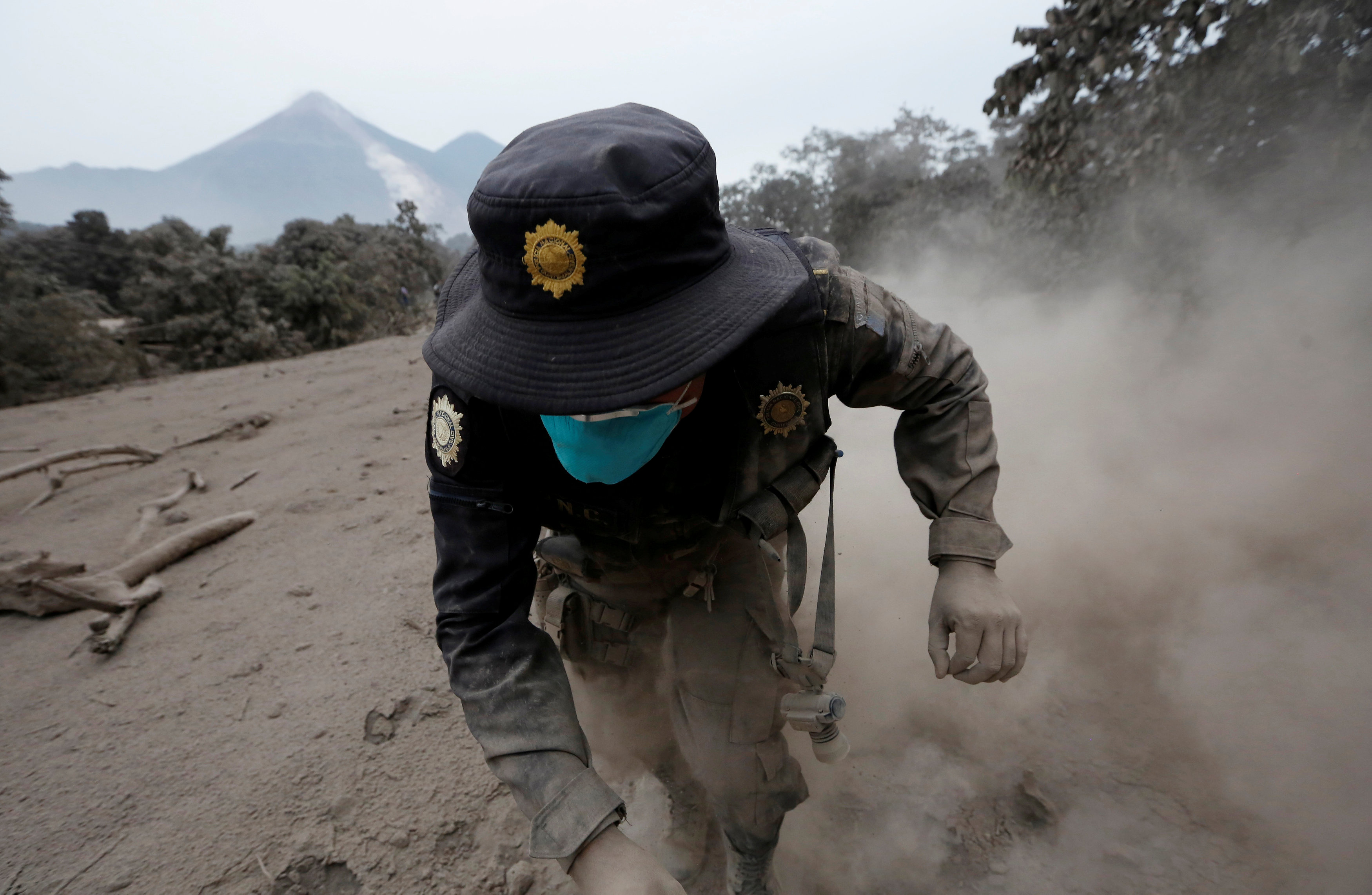 A police officer stumbles while running away after the Fuego volcano spew new pyroclastic flow in the community of San Miguel Los Lotes in Escuintla, Guatemala, June 4, 2018. REUTERS/Luis Echeverria