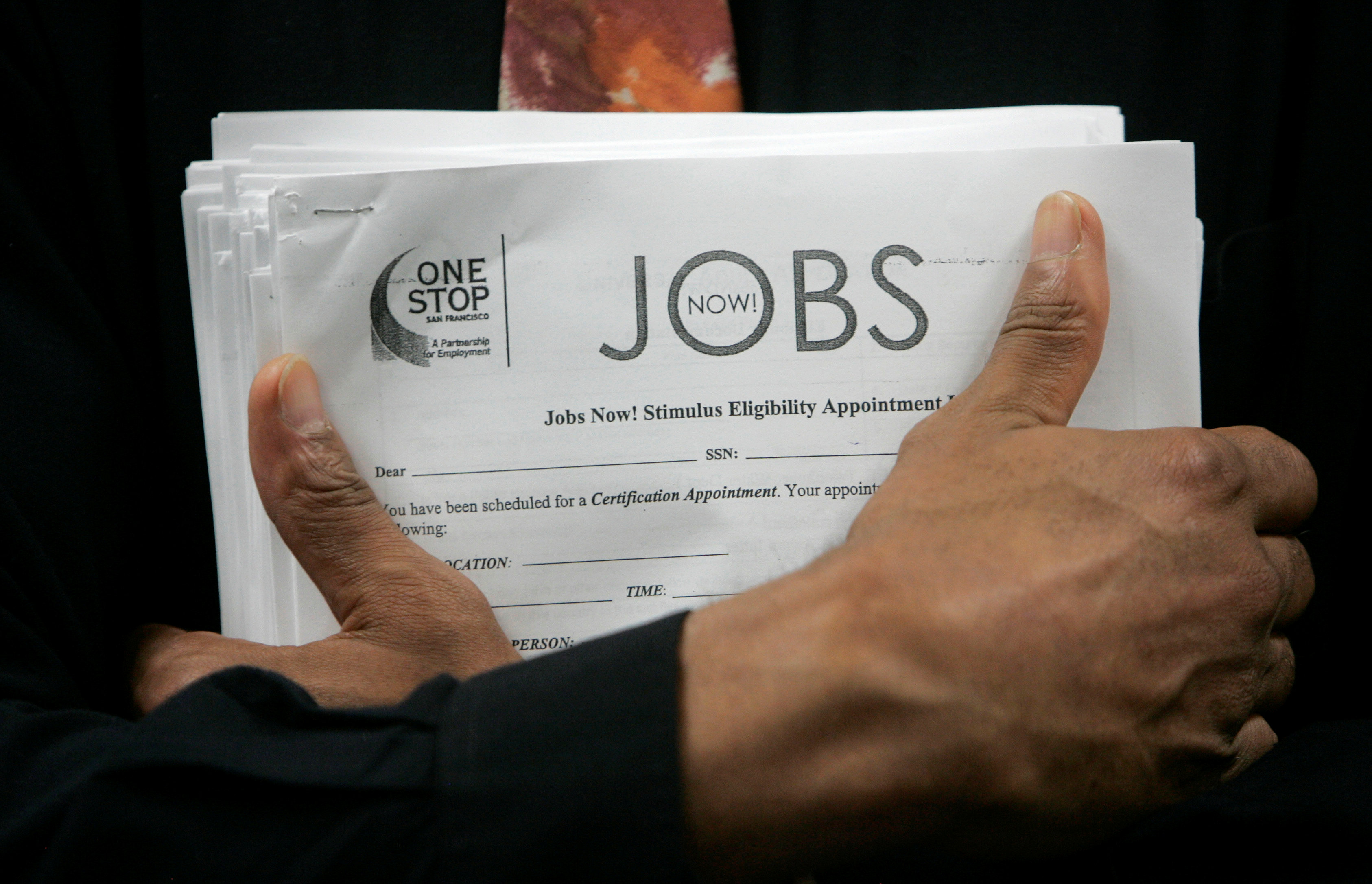 FILE PHOTO: A man carrying a stack of job listings listens to a discussion at the One Stop employment center in San Francisco, California, August 12, 2009. REUTERS/Robert Galbraith/File Photo