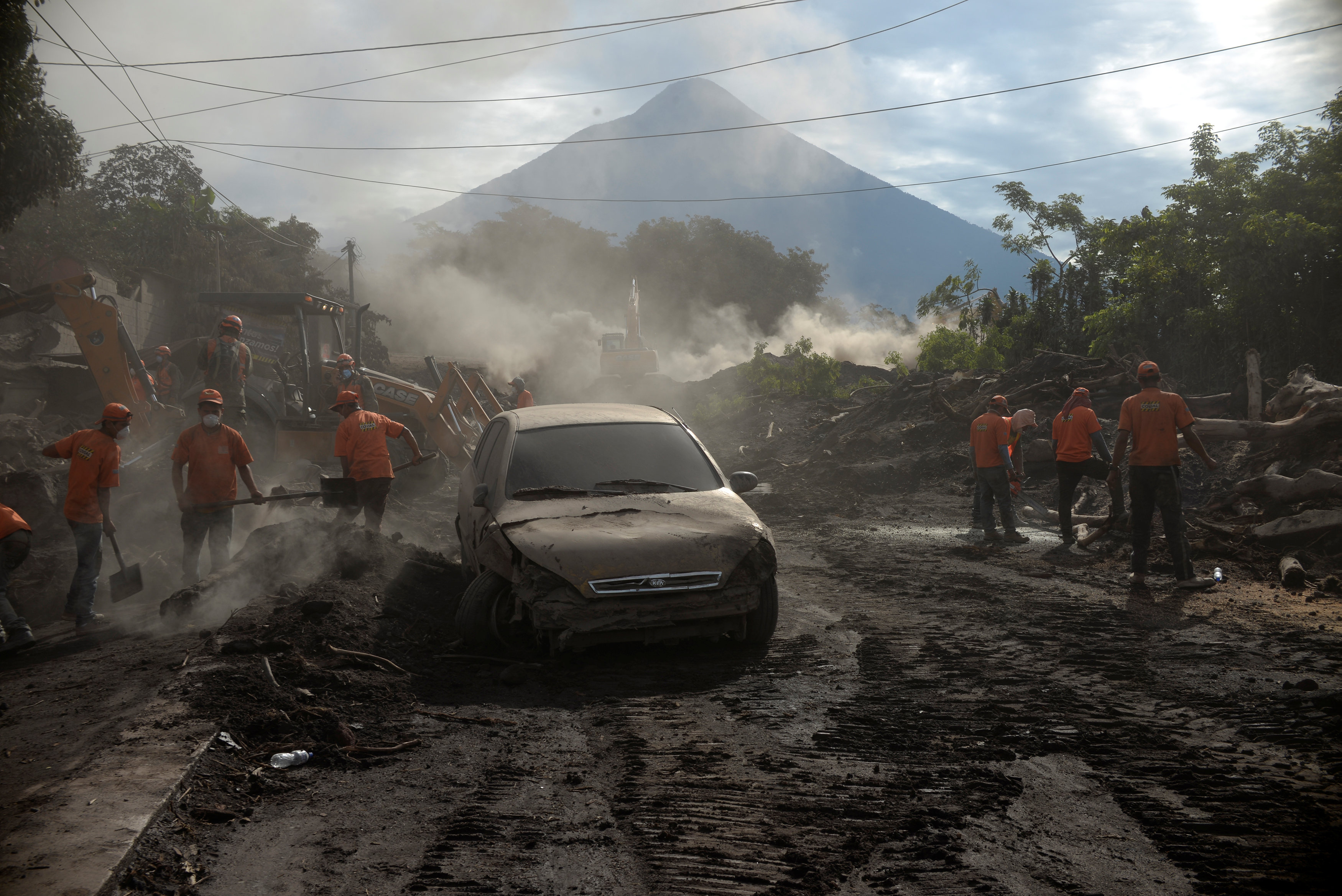 Workers remove ashes from a road at an area affected by the eruption of the Fuego volcano at El Rodeo in Escuintla, Guatemala June 6, 2018. REUTERS/Fabricio Alonzo