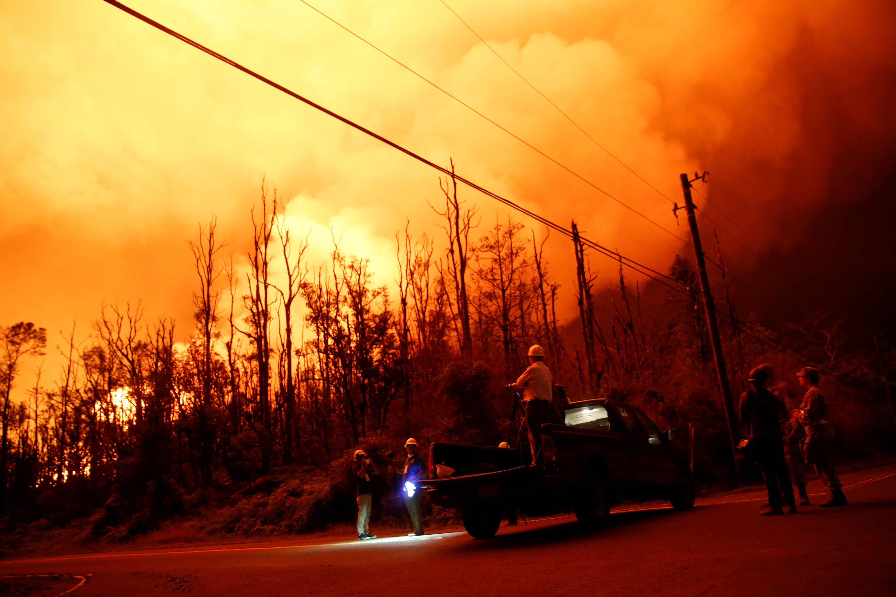 FILE PHOTO: Journalists and National Guard soldiers watch as lava erupts in Leilani Estates during ongoing eruptions of the Kilauea Volcano in Hawaii, U.S., June 9, 2018. REUTERS/Terray Sylvester