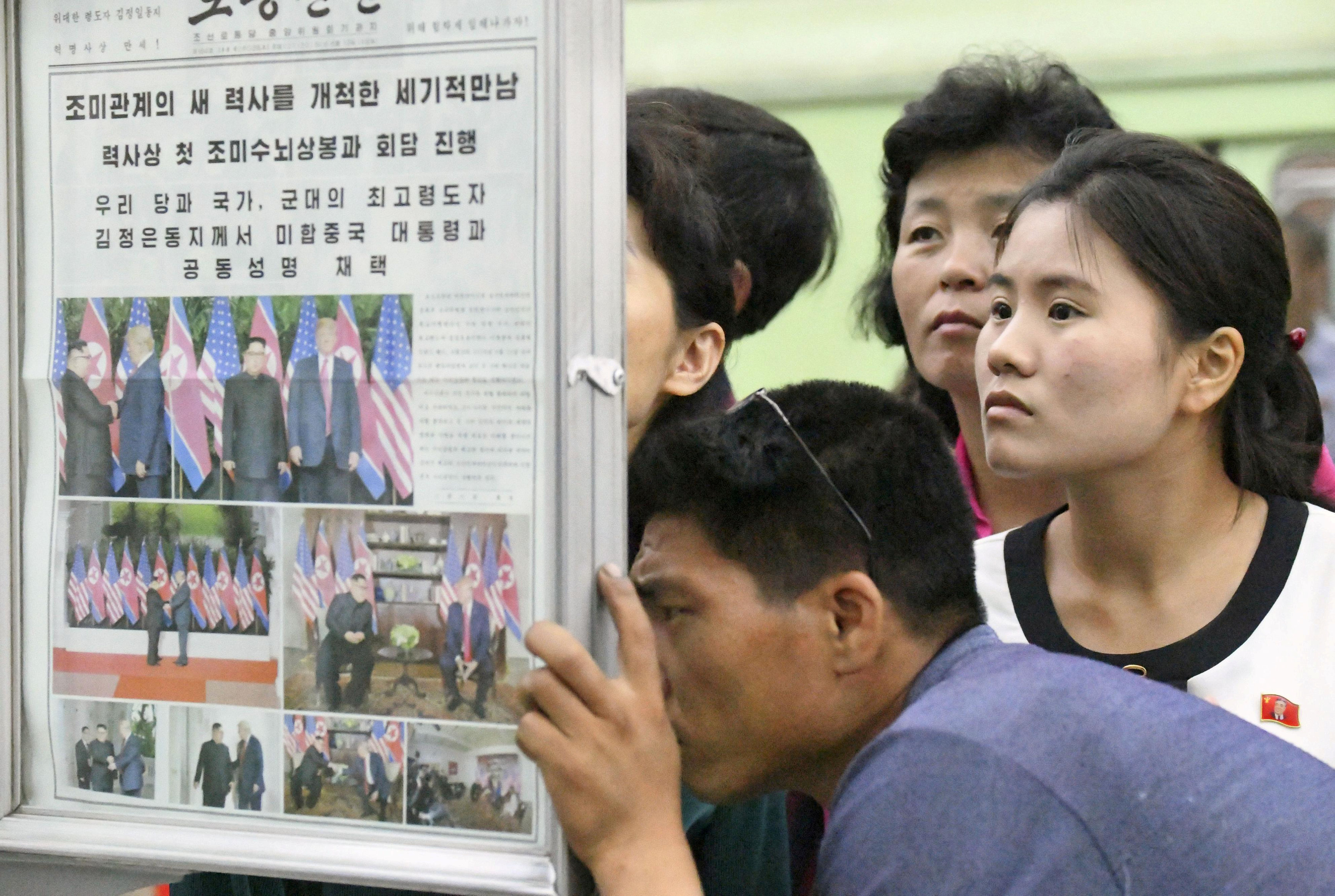 North Koreans watch the displayed local newspapers reporting the summit between the U.S. and North Korea at a subway station in Pyongyang, North Korea, in this photo taken by Kyodo June 13, 2018. Mandatory credit Kyodo/via REUTERS