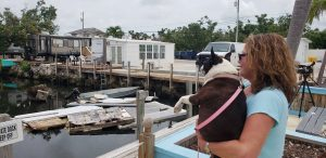 Terri Metter and her Boston Terrier Nikki overlook what's left of destroyed trailers that fill a canal near a trailer park in Marathon, Florida, U.S., June 10, 2018. REUTERS/Zach Fagenson