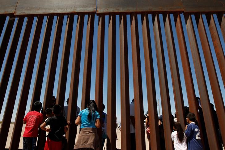 Children interact with members of the Presbyterian church in Sunland Park, U.S. at a new section of the border wall on the U.S.-Mexico border after a liturgy to commemorate the religious dimensions of migration, in this picture taken from Anapra neighborhood in Ciudad Juarez, Mexico May 3, 2018. REUTERS/Jose Luis Gonzalez