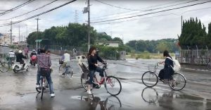 People cycle on a flooded road damaged after an earthquake hit Osaka, Japan June 18, 2018, in this still image taken from a video obtained from social media. MANDATORY CREDIT. Twitter/@tw_hds/via REUTERS