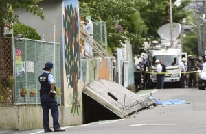 A police officer stands guard at the site where a girl was killed by fallen wall caused by an earthquake at an elementary school in Takatsuki, Osaka prefecture, western Japan, in this photo taken by Kyodo June 18, 2018. Mandatory credit Kyodo/via REUTERS ATTENTION EDITORS - THIS IMAGE WAS PROVIDED BY A THIRD PARTY. MANDATORY CREDIT. JAPAN OUT. NO COMMERCIAL OR EDITORIAL SALES IN JAPAN.