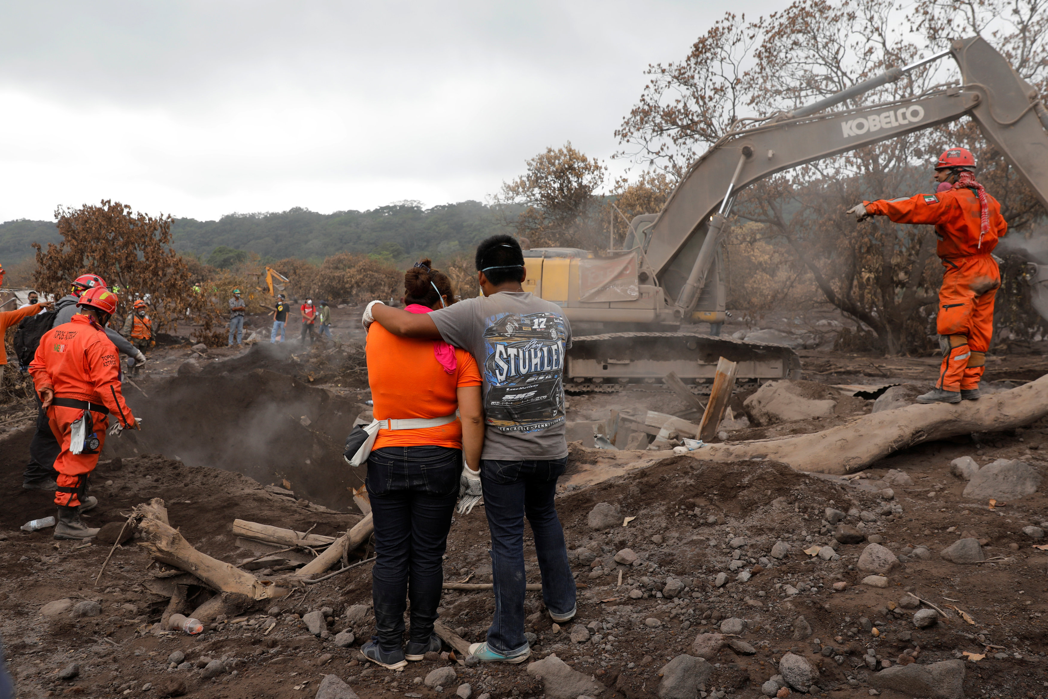 Eva Ascon, is embraced by a family member as rescue workers search for her rest of her family at the affected by the Fuego volcano at San Miguel Los Lotes in Escuintla, Guatemala June 15, 2018. REUTERS/Carlos Jasso