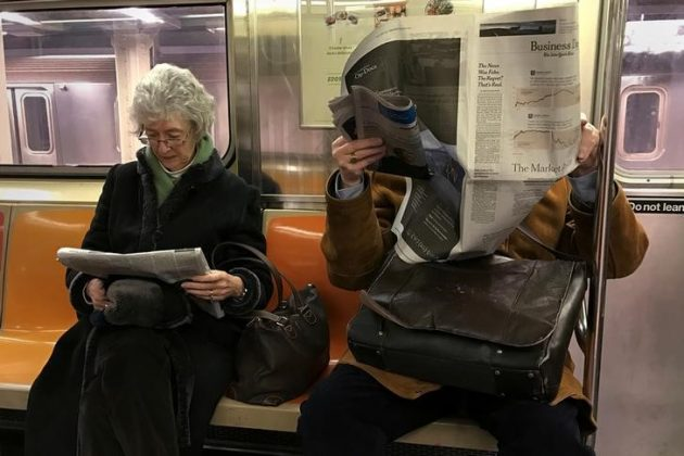 A couple of people ride the subway as they read newspapers as the train pulls into the Times Square stop in Manhattan, New York, U.S. February 17, 2017. REUTERS/Carlo Allegri