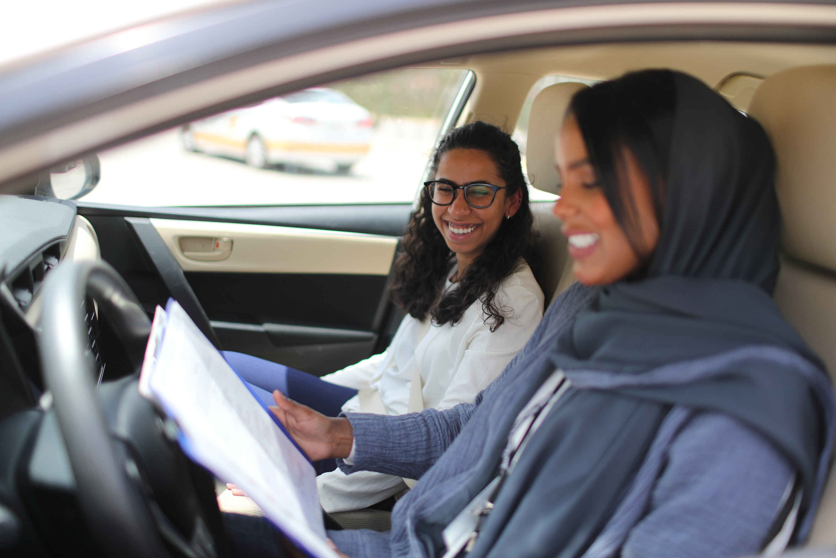 Driving instructor Ahlam al-Somali (R) reads instructions before getting ready to drive with trainee Maria al-Faraj at Saudi Aramco Driving Center in Dhahran, Saudi Arabia, June 6, 2018. REUTERS/Ahmed Jadallah