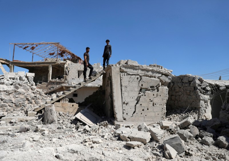 FILE PHOTO: Men inspect a damaged house in Busra al-Harir town, near Deraa, Syria March 13, 2018. REUTERS/Alaa al-Faqir/File Photo
