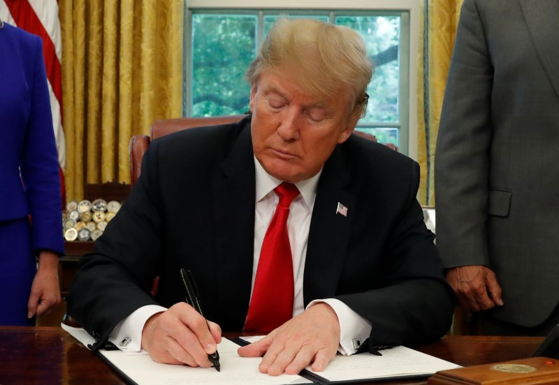U.S. President Donald Trump signs an executive order on immigration policy in the Oval Office of the White House in Washington, U.S., June 20, 2018. REUTERS/Leah Millis