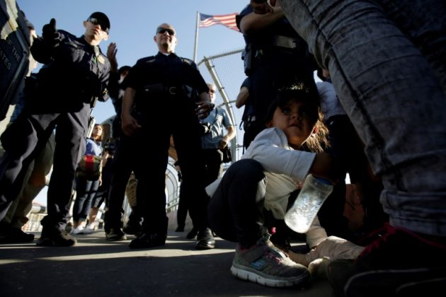 Migrant families from Mexico, fleeing from violence, listen to officers of the U.S. Customs and Border Protection before entering the United States to apply for asylum at Paso del Norte international border crossing bridge in Ciudad Juarez, Mexico. REUTERS/Jose Luis Gonzalez