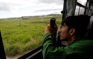 A tourist from Tokyo's university, takes photos from a bus at an area devastated by the March 11, 2011 earthquake and tsunami, near Tokyo Electric Power Co's (TEPCO) tsunami-crippled Fukushima Daiichi nuclear power plant, in Namie town, Fukushima prefecture, Japan May 19, 2018. Picture taken May 19, 2018. REUTERS/Toru Hanai