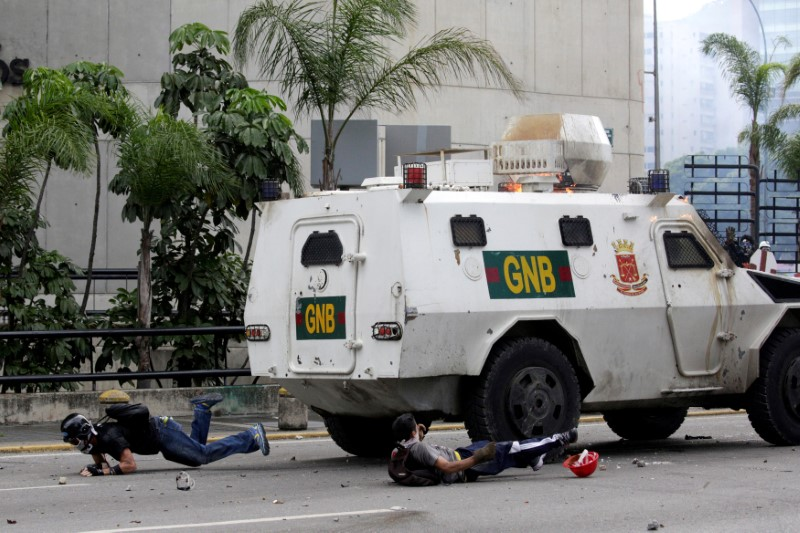 Demonstrators fall on the ground after being hit by a riot police armoured vehicle while clashing with the riot police during a rally against Venezuelan President Nicolas Maduro in Caracas, Venezuela, May 3, 2017. REUTERS/Marco Bello/File Photo