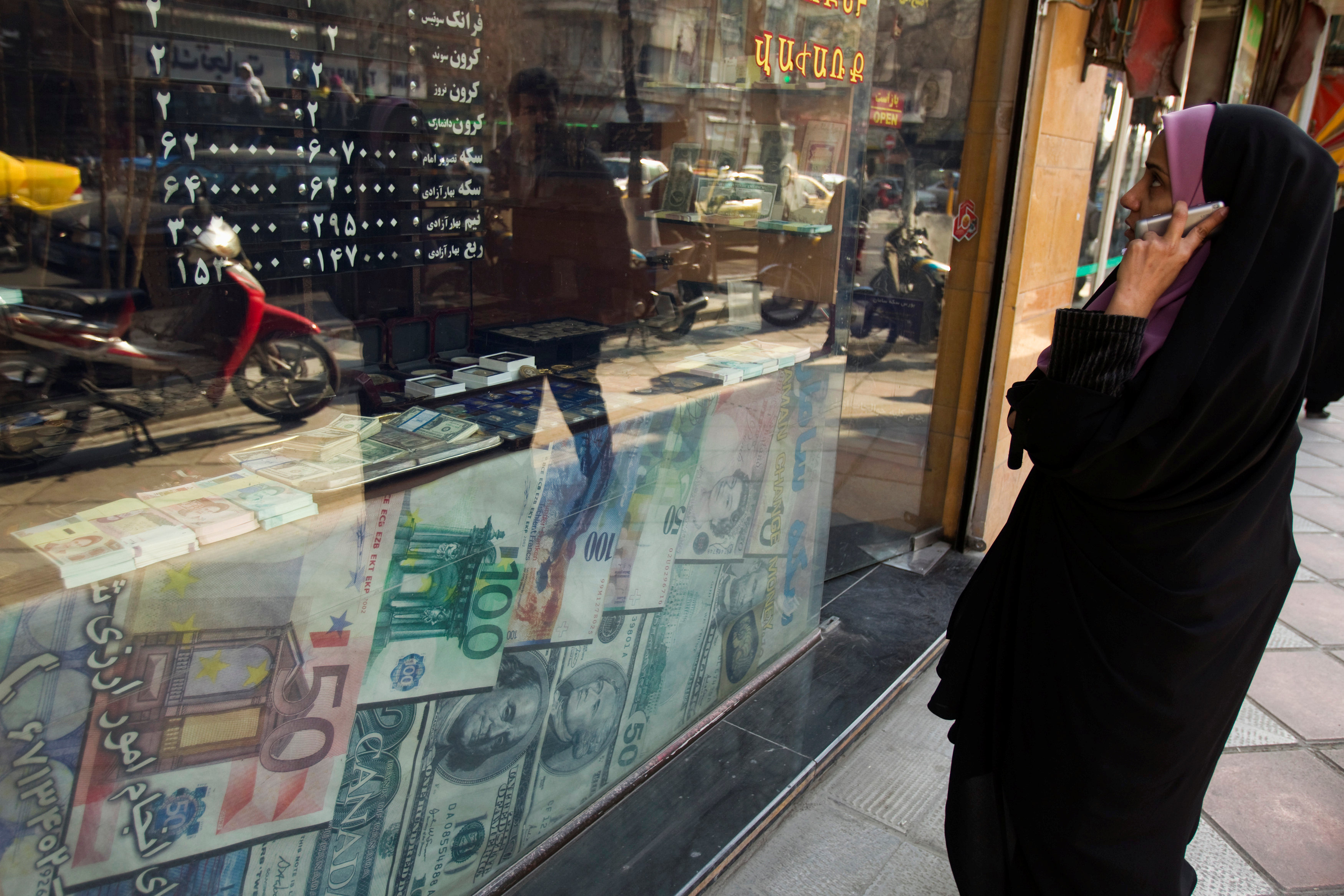 FILE PHOTO: A woman looks at exchange rates by the window of a currency exchange shop in Tehran's business district, Iran January 7, 2012. REUTERS/Raheb Homavandi /File Photo