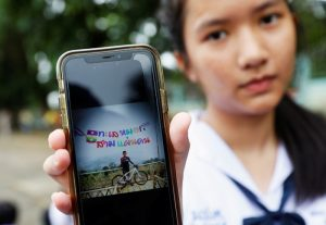 A student shows a photo of her classmate Prachak Sutham, 13, who is a member of an under-16 soccer team that went missing with their coach at a flooded cave, in Mae Sai Prasitsart school in the northern province of Chiang Rai, Thailand, July 2, 2018. REUTERS/Soe Zeya Tun