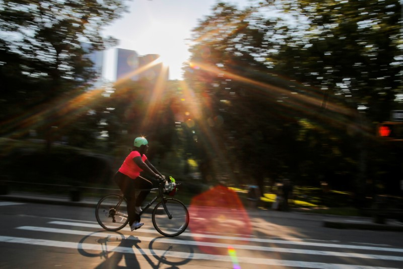A woman rides a bike on a hot summer day in Central Park, Manhattan, New York, U.S., July 1, 2018. REUTERS/Eduardo Munoz