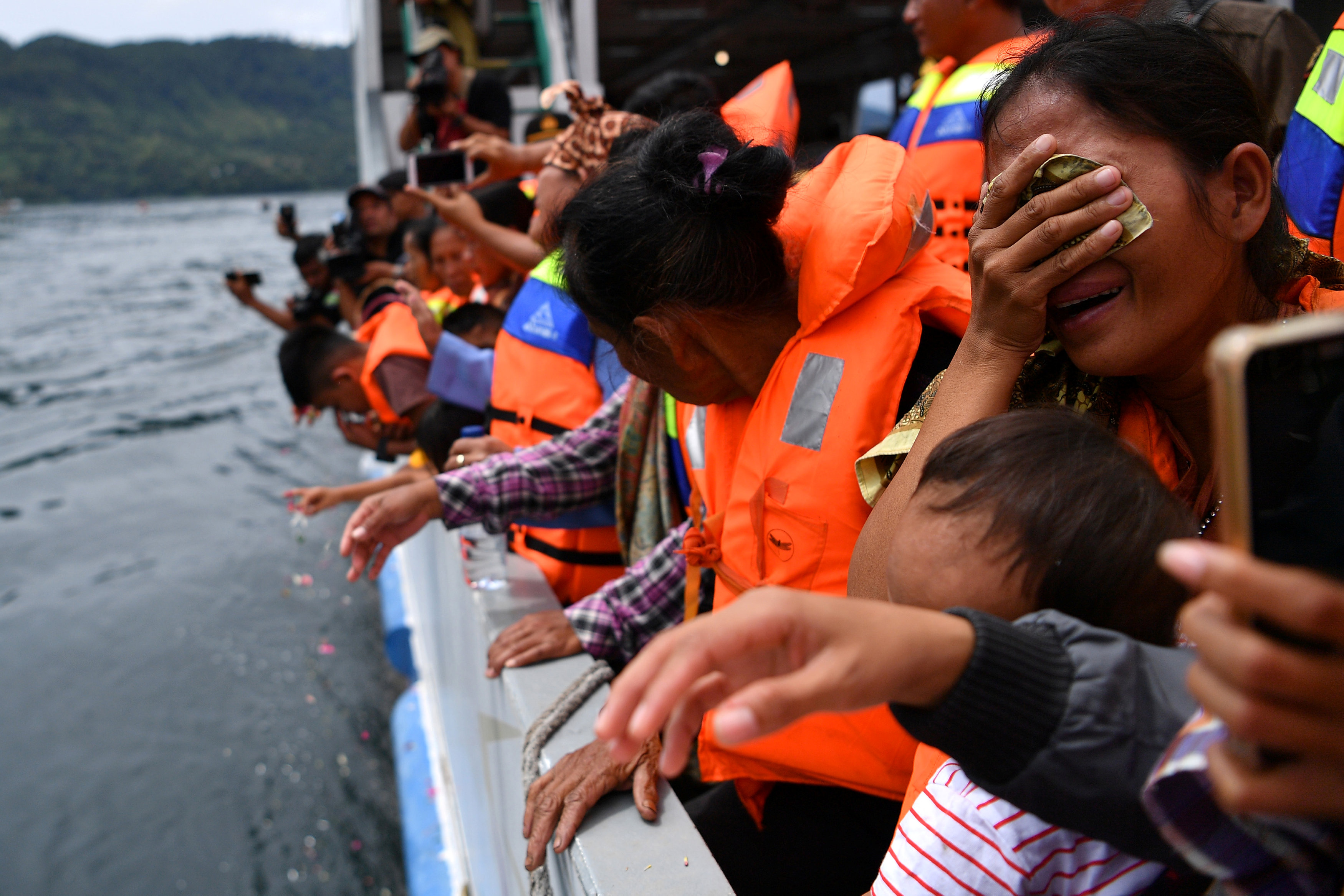 Relatives of missing passengers react during a visit to the location of the ferry that sank at Lake Toba in Simalungun, North Sumatra, Indonesia July 2, 2018. Antara Foto/Sigid Kurniawan/via REUTERS