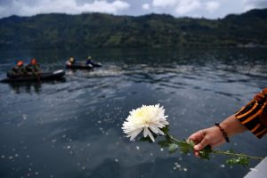 A relative of missing passengers of a ferry that sank holds a flower before throwing it into Lake Toba in Simalungun, North Sumatra, Indonesia July 2, 2018. Antara Foto/Sigid Kurniawan/via REUTERS