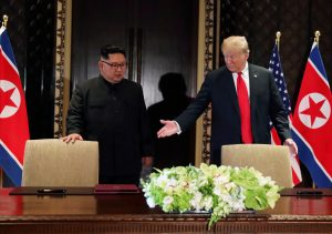 FILE PHOTO: U.S. President Donald Trump and North Korea's leader Kim Jong Un (L) arrive to sign a document to acknowledge the progress of the talks and pledge to keep momentum going, after their summit at the Capella Hotel on Sentosa island in Singapore, June 12, 2018. REUTERS/Jonathan Ernst/File Photo
