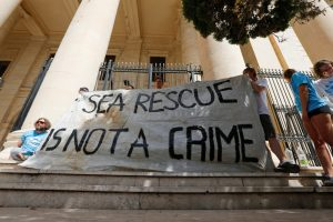 Crew members of NGO Sea-Watch protest outside the Courts of Justice during the arraignment of Claus-Peter Reisch, the captain of the charity ship MV Lifeline in Valletta, Malta July 2, 2018. REUTERS/Darrin Zammit Lupi