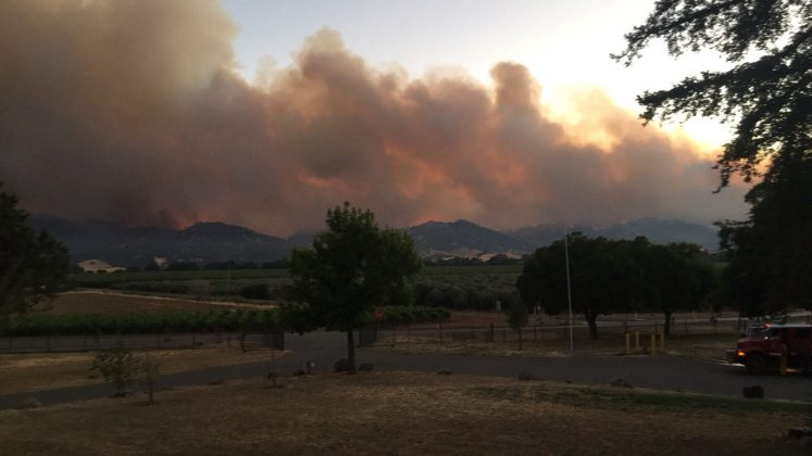 Smoke rises in distance from County Fire near County Road 63 and Highway 16 in Rumsey Canyon in this #CountyFire image on social media in Brooks, California, U.S., July 2, 2018. Courtesy California Department of Forestry and Fire Protection/Handout via REUTERS