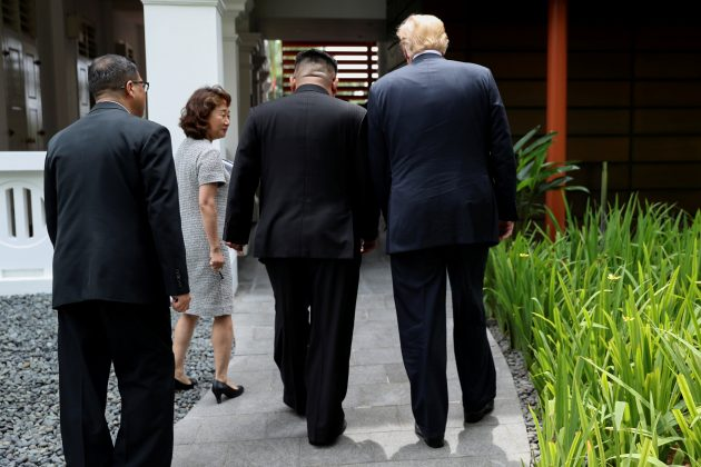 FILE PHOTO: U.S. President Donald Trump and North Korea's leader Kim Jong Un walk together before their working lunch during their summit at the Capella Hotel on the resort island of Sentosa, Singapore June 12, 2018. Picture taken June 12, 2018. REUTERS/Jonathan Ernst