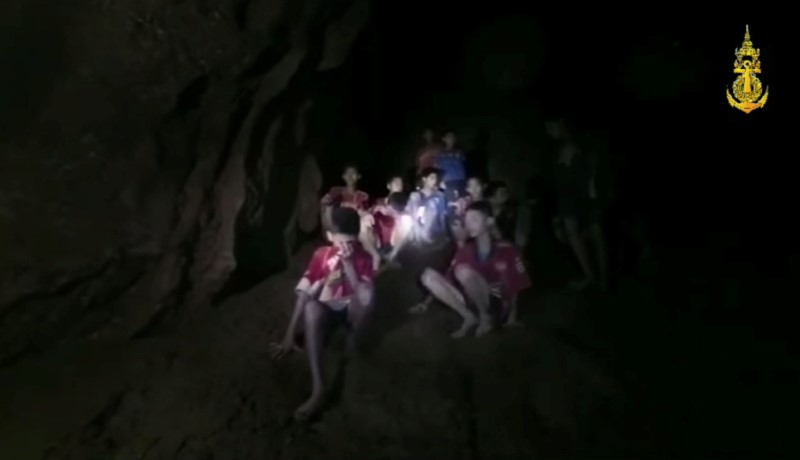 Boys from an under-16 soccer team and their coach wait to be rescued after they were trapped inside a flooded cave in Chiang Rai, Thailand, July 3, 2018, in this still image taken from a Thai Navy Seal handout video. Thai Navy Seal Facebook/Handout via REUTERS
