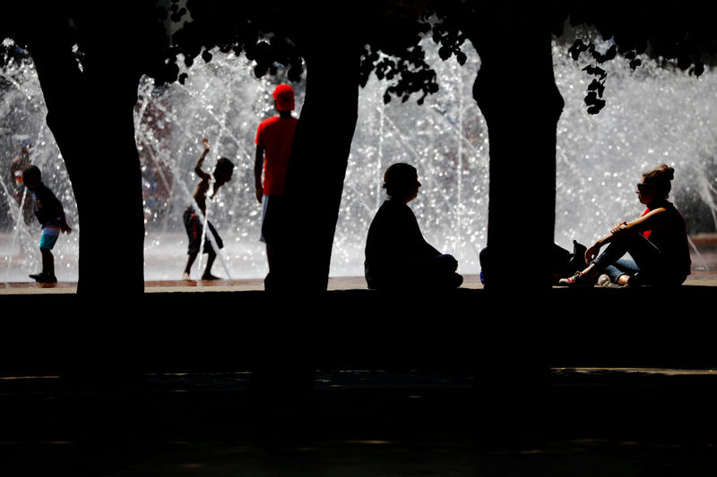 FILE PHOTO: People sit in the shade and cool off in a fountain during a summer heat wave in Boston, Massachusetts, U.S., July 2, 2018. REUTERS/Brian Snyder/File Photo